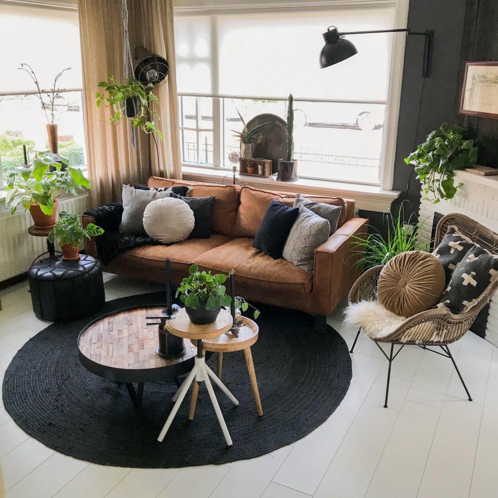 Een prachtige woonkamer met een rond vloerkleed. Stoere elementen als een cognac kleurige bank, industriële lampen etc. Het stijlvol ingericht huis van Arnold en Jorn.